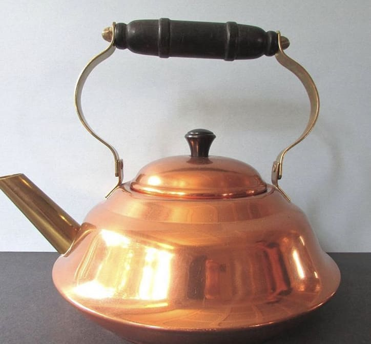 An antique copper tea kettle.
