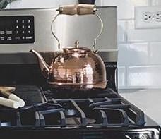 The best copper tea kettle reviews. A copper tea kettle on a gas range.