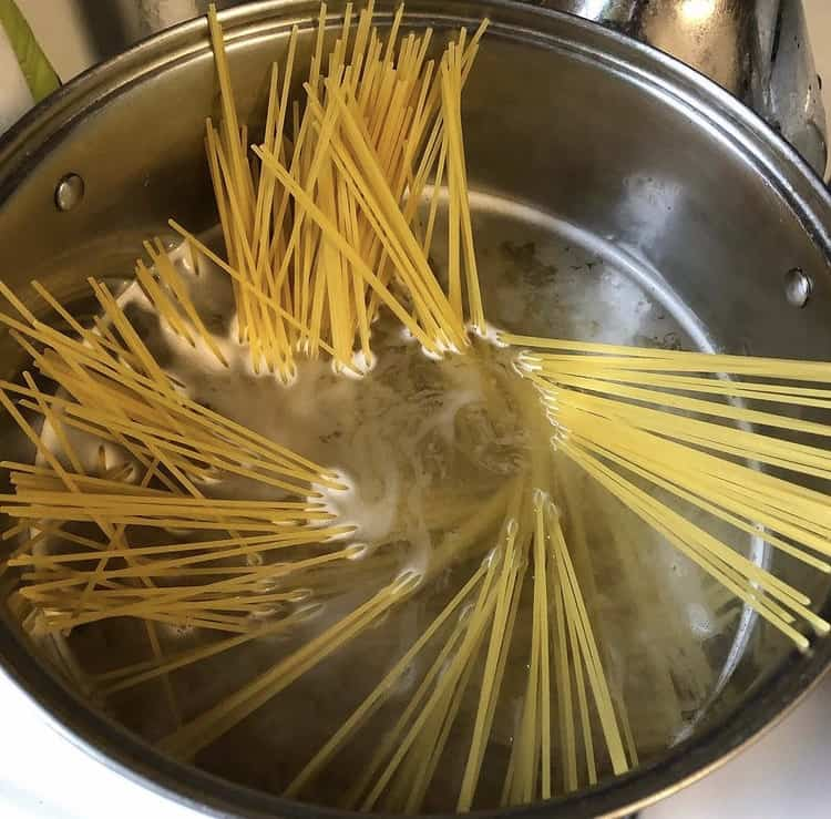 Pasta about to boil inside of a best pasta pot with strainer.