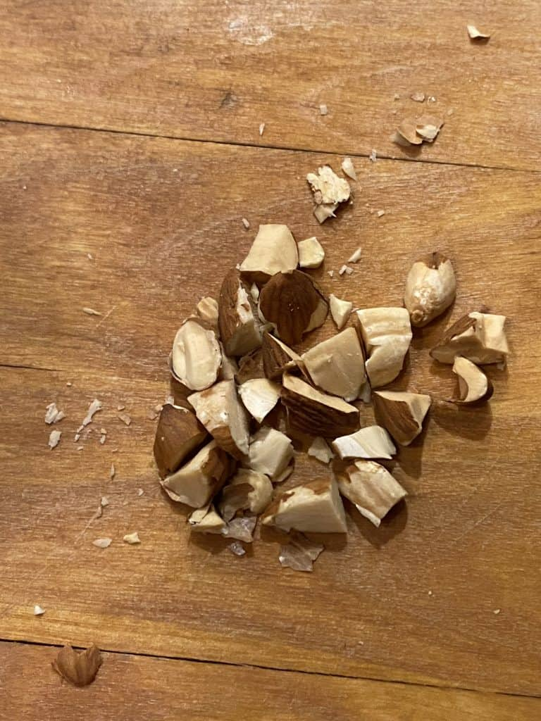 Coarsely chopped almonds on a wooden cutting board.