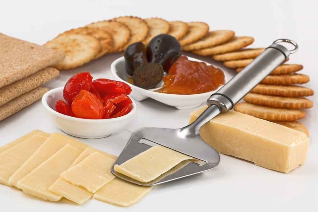 a best cheese slicer on a platter with crackers, peppers, a hard cheese, olives, and jam.
