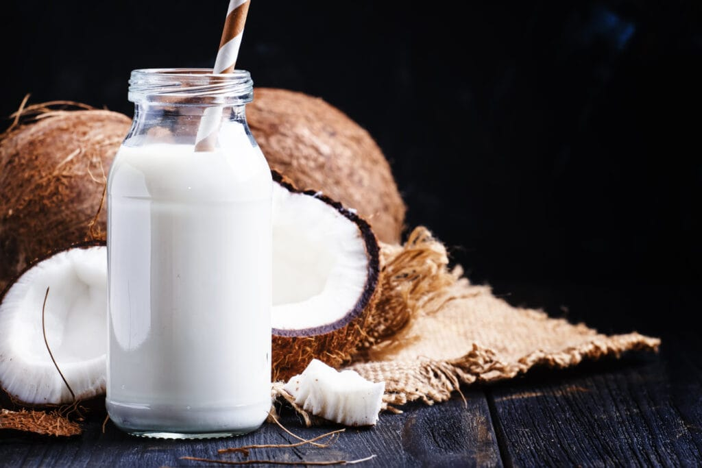 Can you Freeze coconut milk that is fresh? Fresh coconut milk in a glass jar, next to a coconut cut in half.